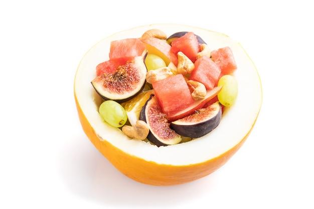 Vegetarische fruitsalade van watermeloen, druiven, vijgen, peer, sinaasappel, cashew geïsoleerd op een witte achtergrond. zijaanzicht, close-up.