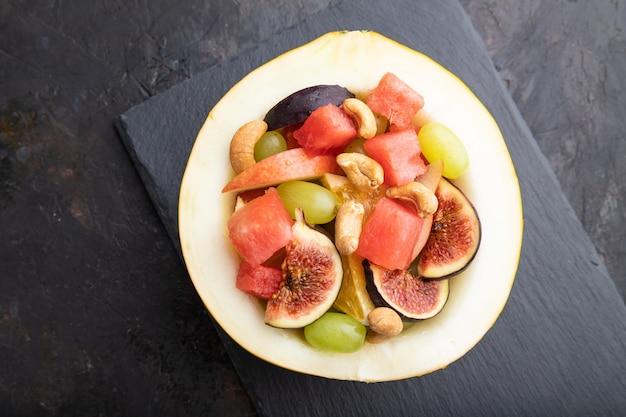 Vegetarische fruitsalade van watermeloen, druiven, vijgen, peer, sinaasappel, cashew op leisteen bord op een zwarte concrete achtergrond. bovenaanzicht, plat leggen, close-up.