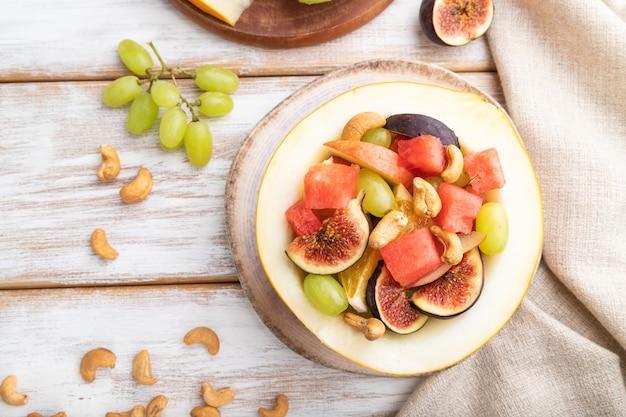 Vegetarische fruitsalade van watermeloen, druiven, vijgen, peer, sinaasappel, cashew op witte houten achtergrond en linnen textiel. bovenaanzicht, plat leggen, close-up.