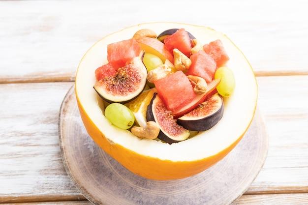 Vegetarische fruitsalade van watermeloen, druiven, vijgen, peer, sinaasappel, cashew op witte houten achtergrond. zijaanzicht, close-up.