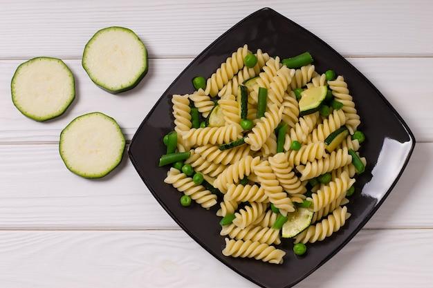 Vegetarische fusilli pasta met courgette en erwten, in een grijze plaat, op een houten achtergrond
