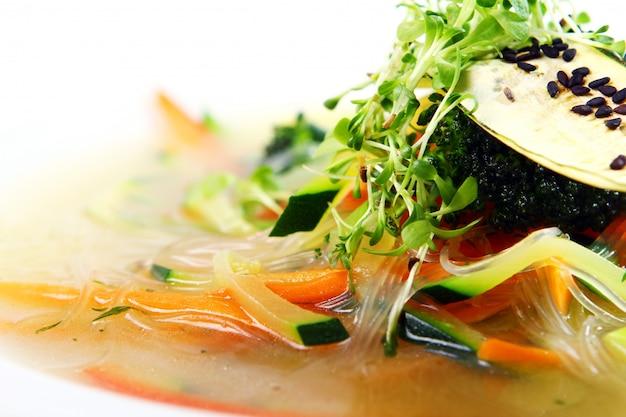 Vegetarische gastronomische soep met witte achtergrond