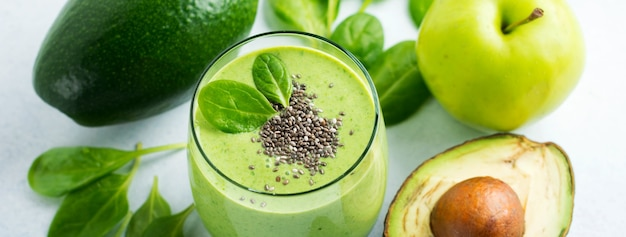 Vegetarische gezonde groene smoothie van avocado, spinaziebladeren, appel en chiazaden in glas op grijze betonnen ondergrond. selectieve aandacht. ruimte voor tekst. banier.