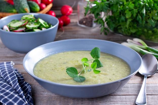 Vegetarische gezonde soep, groene erwtenroomsoep met olijfolie op houten tafel