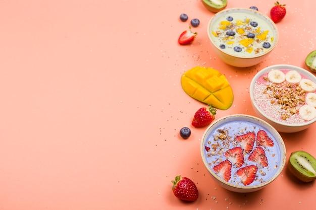 Vegetarische gezonde voeding gemaakt van multi-gekleurde smoothies met lucifers en bessen op een fel roze tafel.