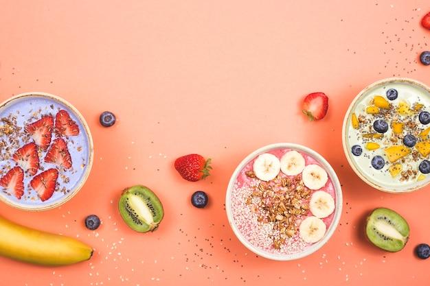 Vegetarische gezonde voeding gemaakt van multi-gekleurde smoothies met lucifers en bessen op een heldere pinktable.