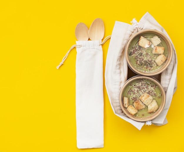 Vegetarische groene roomsoep in een ambachtelijke container voor afhaalmaaltijden