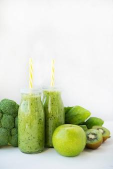 Vegetarische groene smoothie met groenten en fruit in glazen flessen, kopie ruimte