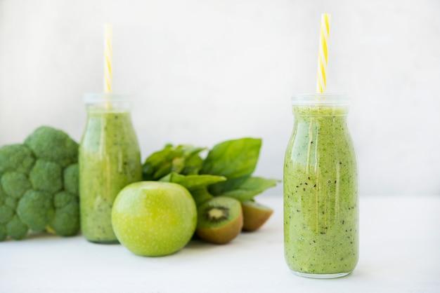 Vegetarische groene smoothie met groenten en fruit in glazen flessen, selectieve aandacht