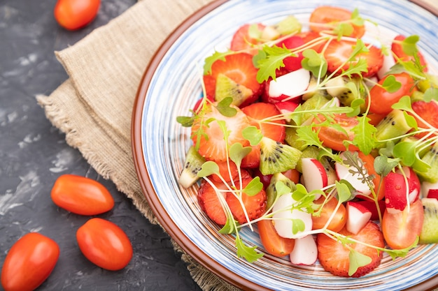 Vegetarische groenten en fruit salade van aardbei, kiwi, tomaten, microgreen spruiten op zwarte betonnen ondergrond en linnen textiel