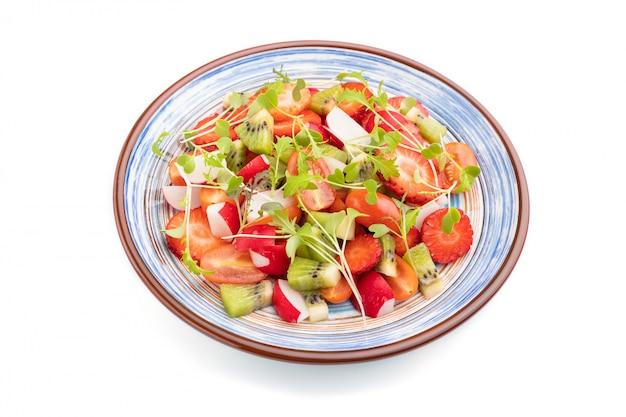 Vegetarische groenten en fruit salade van aardbeien, kiwi, tomaten, microgroene spruiten geïsoleerd op een witte achtergrond. zijaanzicht.