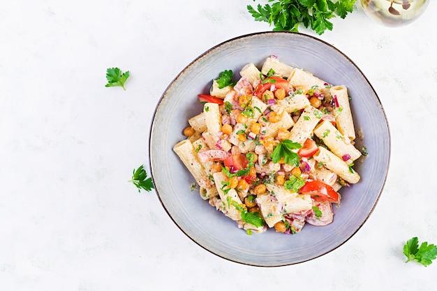 Vegetarische groentepasta. pasta rigatoni met tomaat, rode ui, peterselie en gebakken kikkererwten met notensaus. veganistisch eten. bovenaanzicht, overhead