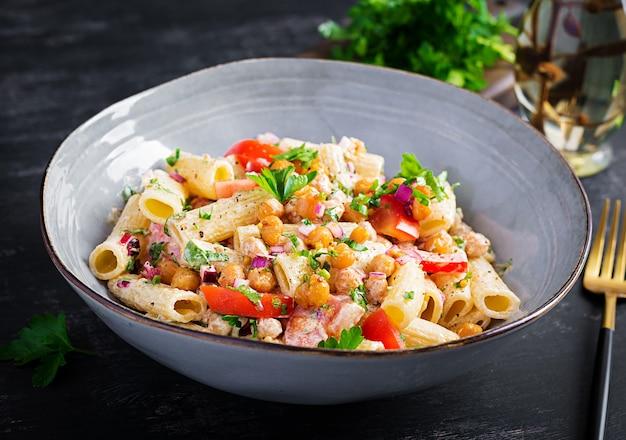 Vegetarische groentepasta. pasta rigatoni met tomaat, rode ui, peterselie en gebakken kikkererwten met notensaus. veganistisch eten.
