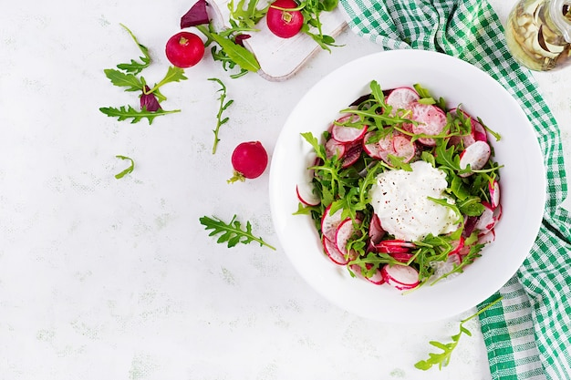 Vegetarische groentesalade van radijs en rucola met zure room