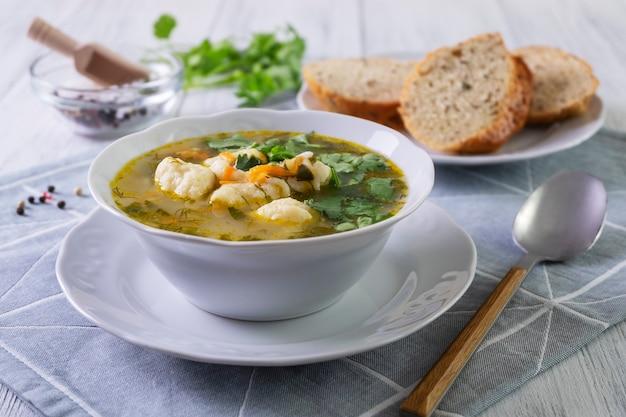 Vegetarische groentesoep met dumplings in een wit porseleinen bord. gezonde en dieetvoeding. vegetarisme. selectieve aandacht, close-up.