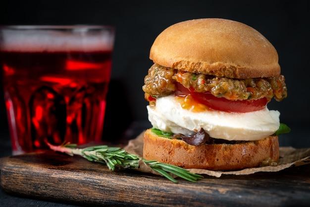 Vegetarische hamburger gemaakt van gebakken aubergine, tomaat, sla, avocado en mozzarellakaas op een houten bord