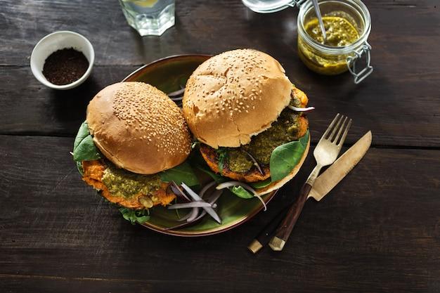 Vegetarische hamburger pompoen spinazie rucola pesto houten tafel gezonde voeding plaat
