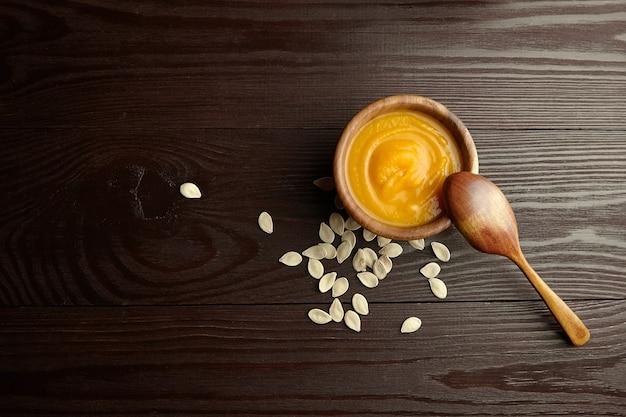 Vegetarische herfst pompoenroomsoep met pompoenpitten in kom met lepel op houten tafel, bovenaanzicht