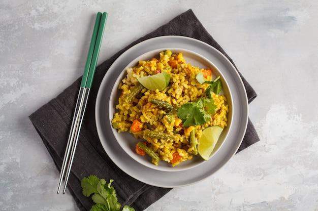 Vegetarische kerrie rijst met groenten in een grijze plaat. bovenaanzicht, kopieer ruimte. gezond veganistisch voedselconcept, detox, plantaardig dieet.