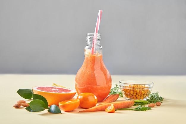 Vegetarische kleurrijke oranje cocktail van biologische groenten, fruit en bessen