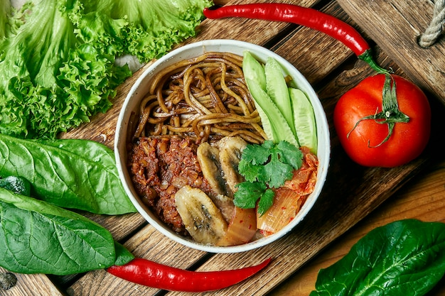 Vegetarische kom met boekweitnoedels, gebakken banaan, komkommer en kimchi op een houten dienblad in een compositie met verse groenten.