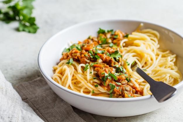Vegetarische linzen bolognese pasta met peterselie in witte schotel.