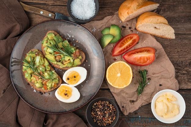Vegetarische lunch met sandwiches met guacamole, gekookte eieren, tomaten en citroen op een houten tafel