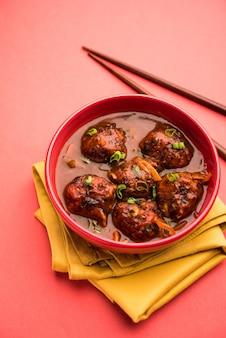 Vegetarische of kip manchurian met jus - populair indiaas eten geserveerd in een kom met eetstokje