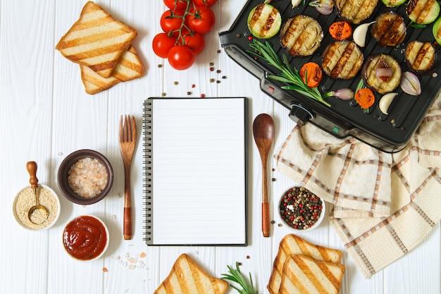 Vegetarische of veganistische gegrilde tafel met barbecue groenten en lege kladblok bovenaanzicht op witte houten achtergrond