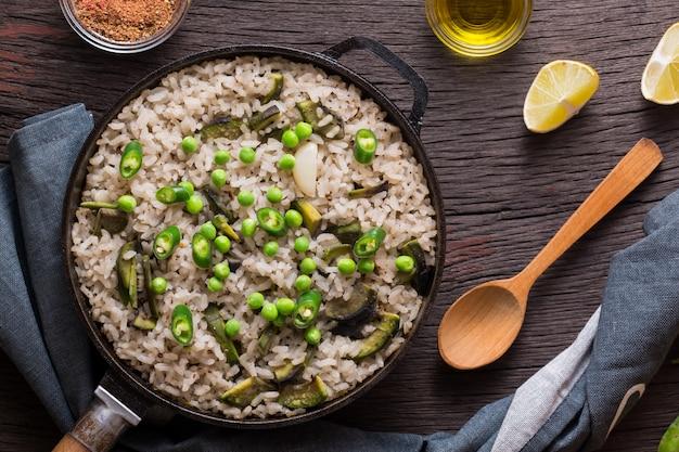 Vegetarische paella met groene erwten en avocado geserveerd in een pan