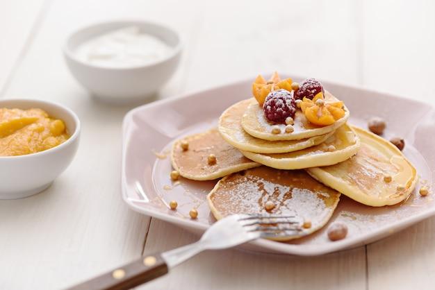 Vegetarische pannenkoeken met honing, frambozen en physalis, bestrooid met poedersuiker met zure room en jam op witte achtergrond