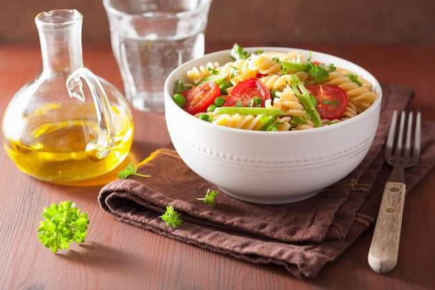 Vegetarische pasta fusilli met tomaten erwten kruiden