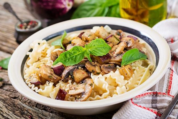 Vegetarische pasta met champignons en aubergines, aubergines. italiaans eten. veganistische maaltijd.