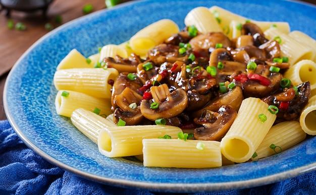 Vegetarische pasta rigatoni met champignons en chili pepers in blauwe kom op houten tafel. veganistisch eten.