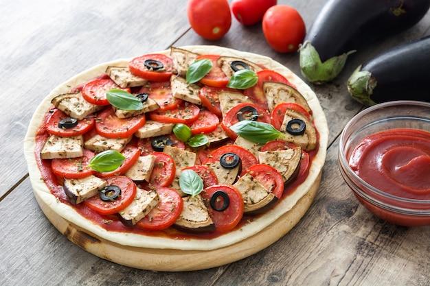 Vegetarische pizza met aubergine, tomaat, zwarte olijven, oregano en basilicum op houten tafel