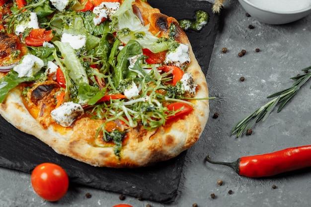 Vegetarische pizza met kaastomaten en greens.