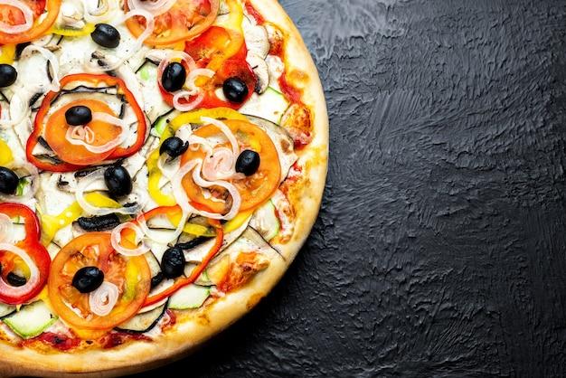 Vegetarische pizza op zwarte achtergrond, op basis van tomaten met mozzarella, olijven, tomaten, aubergine, paprika, courgette, ui en champignons op een houten standaard