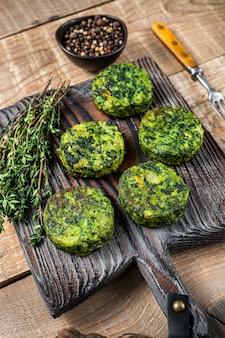 Vegetarische plantaardige hamburgers pasteitje met kruiden op een houten bord