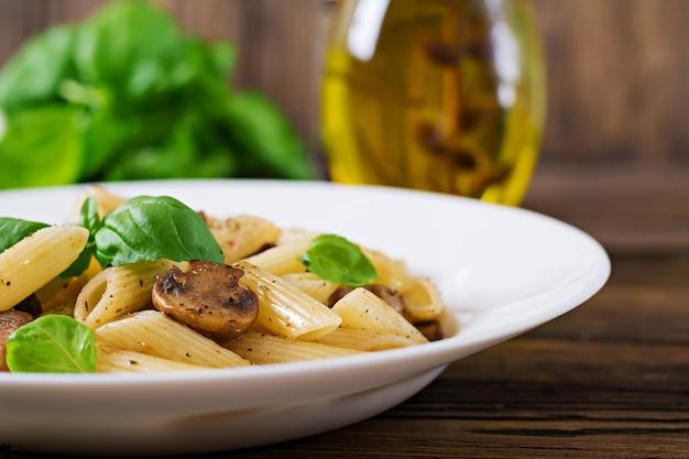 Vegetarische plantaardige pasta penne met champignons in witte kom op houten tafel. veganistisch eten.