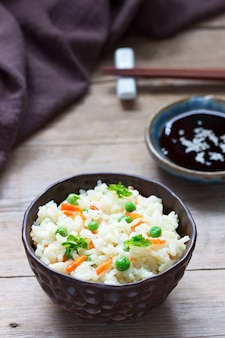 Vegetarische rijstgerecht met groenten en groene erwten op een houten oppervlak