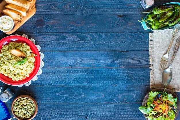 Vegetarische risotto met verschillende groenten op houten rustieke tafel.