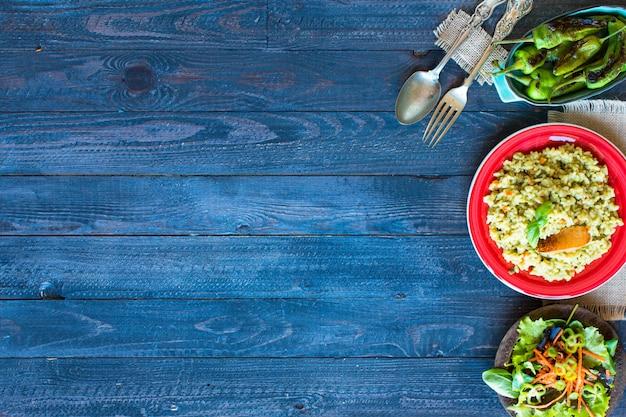 Vegetarische risotto met verschillende groenten, op houten rustieke tafel.