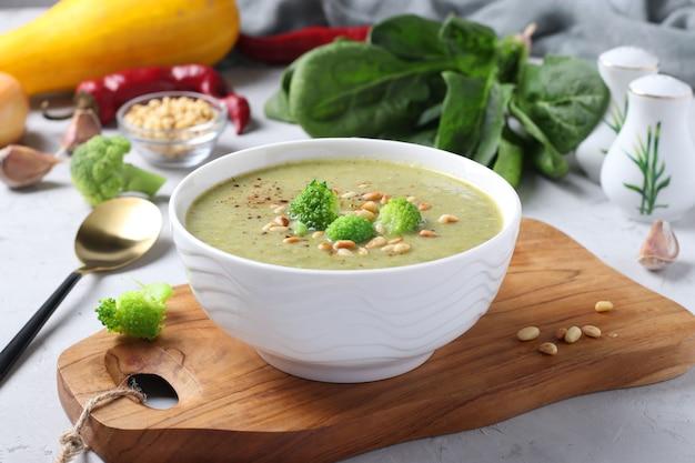 Vegetarische roomsoep met broccoli, spinazie en courgette in witte kom op grijze ondergrond. detailopname.