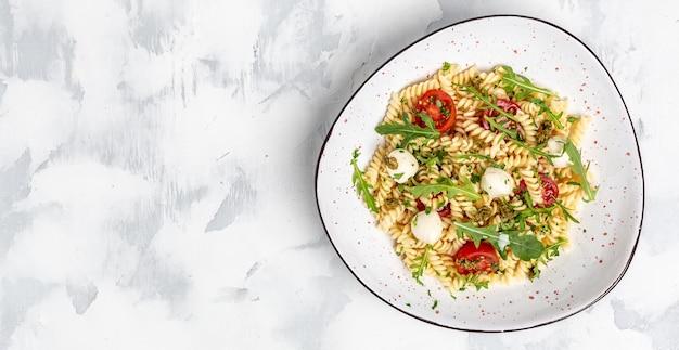 Vegetarische salade, groentepasta salade caprese met kerstomaatjes en mozzarella kaas. lang bannerformaat, bovenaanzicht.
