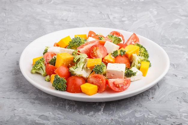 Vegetarische salade met broccoli, tomaten, feta-kaas en pompoen op witte keramische plaat
