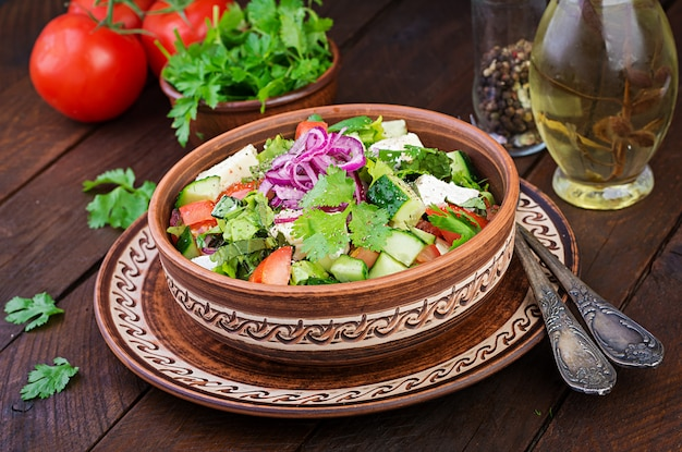 Vegetarische salade met cherrytomaat, brie, komkommer, koriander en rode ui