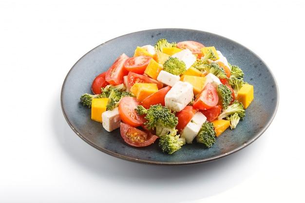 Vegetarische salade met feta-kaas van broccolitomaten en pompoen op een blauwe ceramische plaat die op witte achtergrond wordt geïsoleerd
