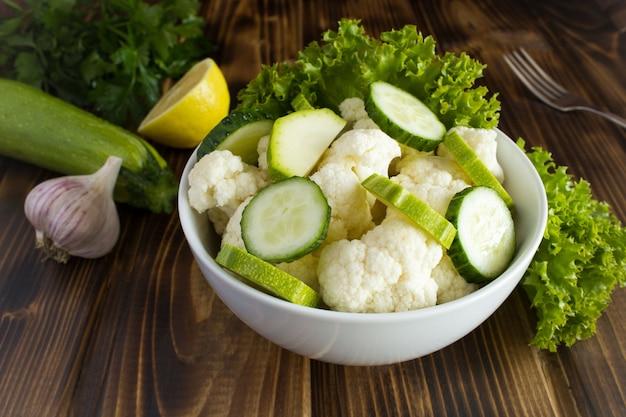 Vegetarische salade met groenten in de witte plaat op de bruine houten achtergrond