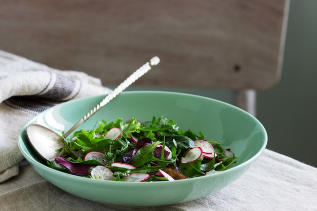 Vegetarische salade met kruiden en radijs op een lichte achtergrond.