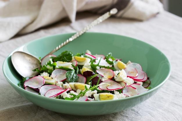 Vegetarische salade met kruiden, radijs, eieren en kwark op een lichte achtergrond.
